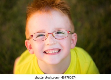 Happy baby boy with red hair in yellow shirt and eyeglasses on happy smiling face summer day outdoor on green natural background