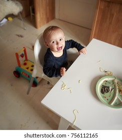 Happy baby boy is sitting by the big white table in the kitchen and eating spaghetti and doing little mess. Child is looking at the camera. View from above.