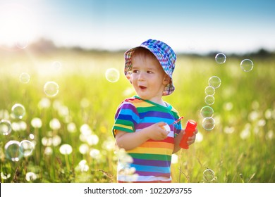 Happy baby boy standing in grass on the field with dandelions at sunny summer evening. child outdoors in nature at sunset blowing bubbles