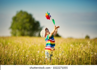 Happy baby boy standing in grass on the fieald with dandelions at sunny summer evening. child outdoors with wind wheel