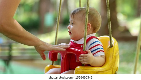Happy baby boy toddler at playground park swing mom pushing son at swing