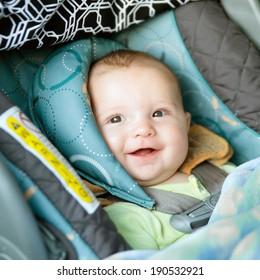 Happy baby buckled into rear-facing car seat