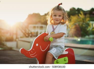 Happy baby child riding a red elephant at the playground
