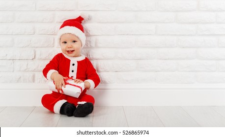 872fed3ad6026 Happy baby in a Christmas costume Santa Claus with gifts on white brick wall
