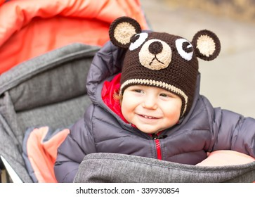 Happy baby in a funny hat on a walk. Walking outdoors in the fall. autumn leaves
