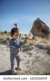 Happy baby girl with a big dandelion in nature. Knowledge of the world in travel.