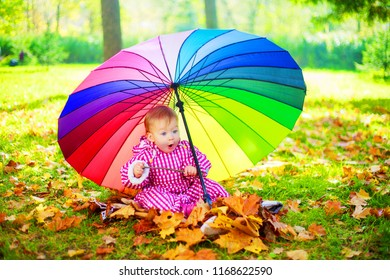 happy baby girl  with a big umbrella in the autumn park