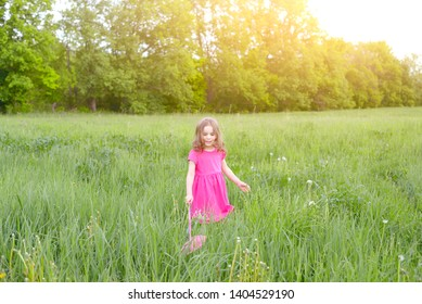Happy baby girl catches butterflies with a pink nipple on a Sunny summer day. Holidays and children's rest concept.