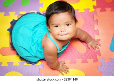 Happy baby girl crawling on a colorful play mat