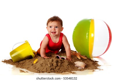A happy baby girl crawling over a sand pile with beach toys, sunglasses and seashells nearby.