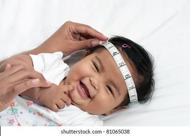 Happy baby girl during routine exam, head measurement