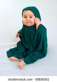 Happy baby girl in green muslim dress sitting