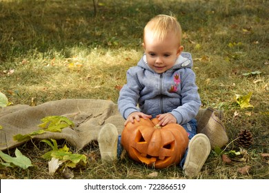 Happy baby girl with Halloween pumpkin in the park.