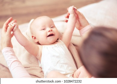 Happy baby girl having fun with mother holding her hands in bed. Motherhood. Happiness.