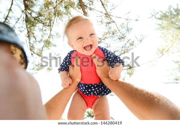 Happy baby girl in her prink and blue bathers in her fathers arms
