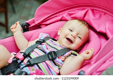 happy baby girl laying  in the stroller