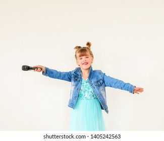 Happy baby girl with microphone smiling singing. Girl in blue dress and denime jacket singing song into microphone. Young star.
