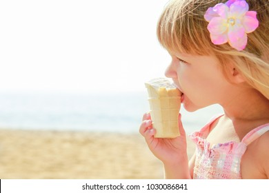 Happy baby girl on the sea in summer eating ice cream outdoors