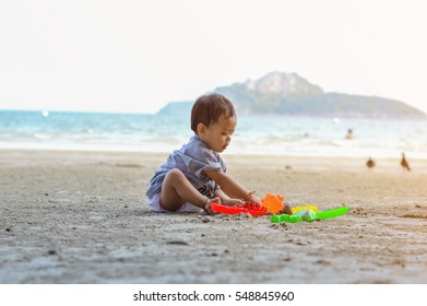Happy baby girl playing on the sandy beach near the sea