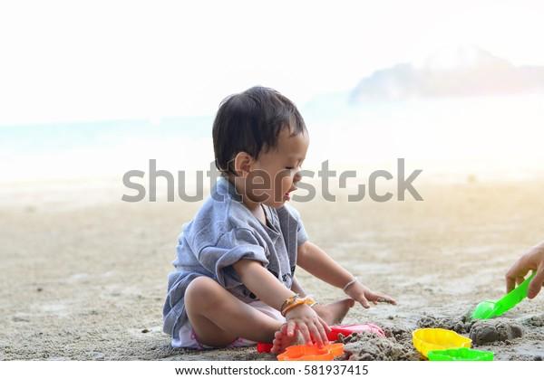 Happy baby girl playing on the sandy beach near the sea