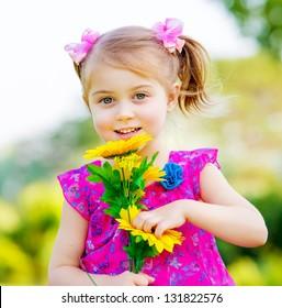 Happy baby girl playing outdoor, cute child holding fresh sunflower flowers, kid having fun in summer park, lovely smiling toddler portrait, enjoying nature of garden