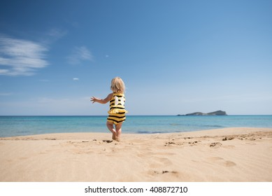 Happy baby girl running on the beach looking at the sea