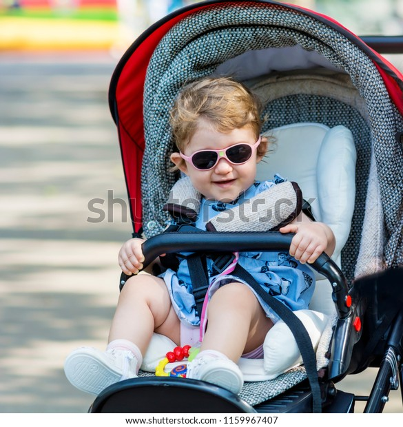 Happy Baby Girl in Baby Stroller Wearing a Sunglasses