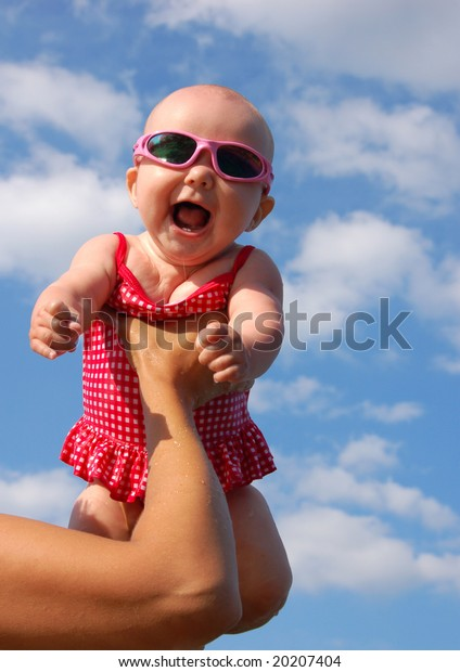Happy Baby girl in swimsuit and sun glasses with the sky as background.