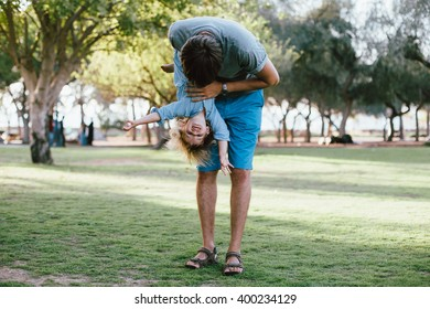 Happy baby girl toddler having fun with her father outdoors in the park