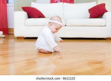 Happy baby girl touching a hardwood floor