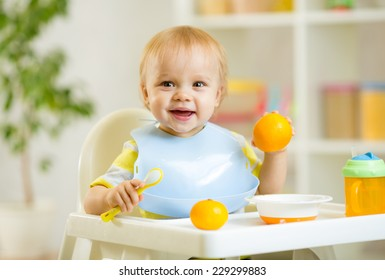 happy baby kid child boy eating healthy food at home