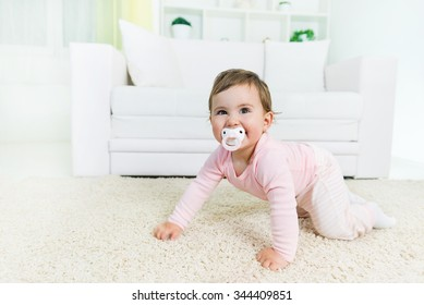 Happy baby little girl crawling with a pacifier in a mouth on the living room floor, looking at camera.Copy space
