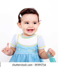 Happy Baby looking at camera with brush in her hands