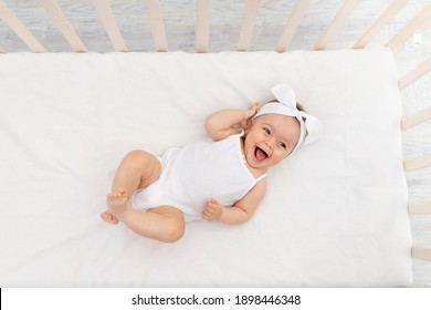 happy baby is lying in a crib in the children's room on a white bed