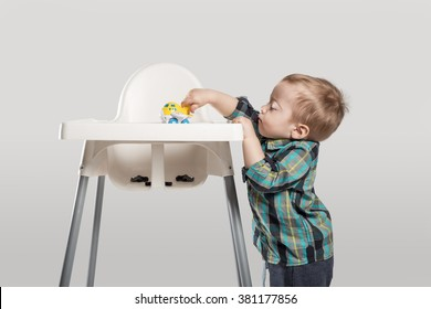 happy baby next to a high children dinning chair