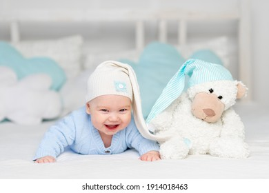 happy baby on the bed in a hood. Textiles and bedding for children. Newborn baby with a toy bear