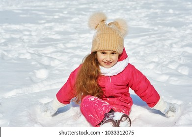 Happy baby on a winter walk .Little girl having fun playing with snow