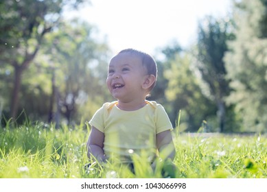 Happy baby in the park, discovering nature for the first time