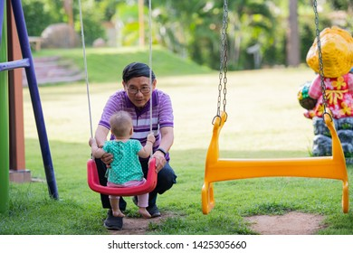 Happy baby playing in colorful playground for kids. Summer family leisure.