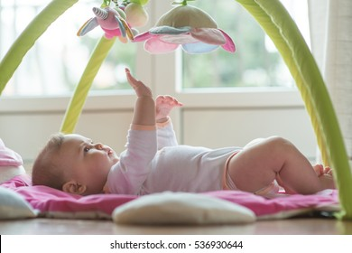 Happy baby playing with hanging toys