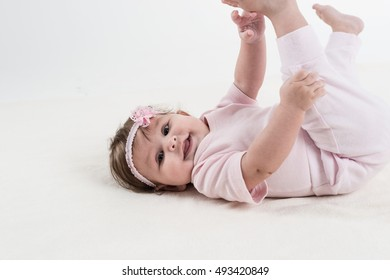 Happy baby is playing on the ground.
