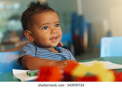Happy baby playing with toy blocks in the kindergarten.
