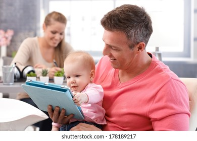 Happy baby reading e-book, sitting on father's lap, mother sitting at background.
