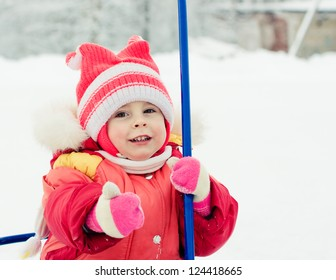 Happy baby in red clothes in winter outdoors