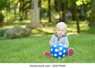 Happy baby sitting in the green grass in park