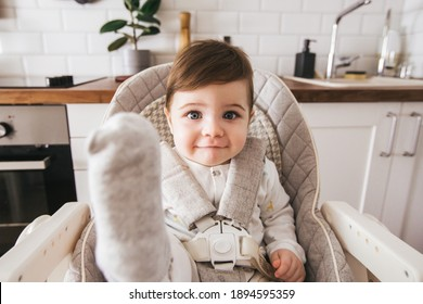 Schönes Baby sitzt auf einem Hochstuhl in einer weißen Küche. Gesunde Ernährung für Kinder. Kinder, die Sicherheit von Kindern. Kleiner Junge spielt und bereit zum Mittagessen auf der Startseite