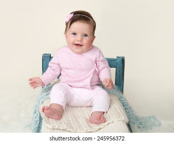 Happy baby sitting on Bed, milestones and development concept