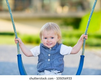 Happy baby sitting on swing