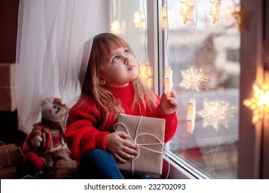 happy baby sitting on the window with Christmas present