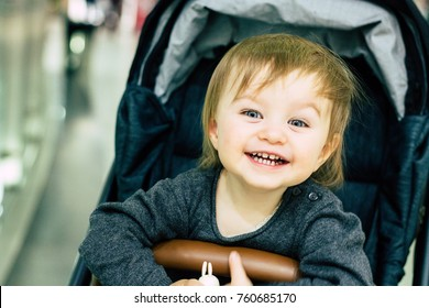 Happy baby sitting in a stroller in shopping mall